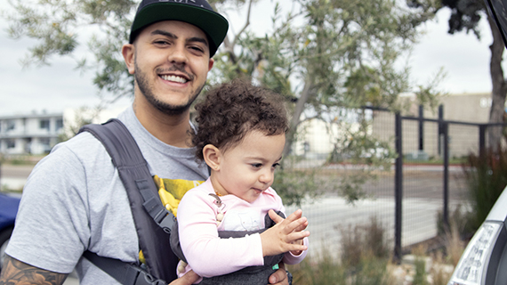 father smiling while carrying his daughter