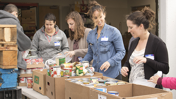 teen volunteers packing food into boxes at Hand Up food drive